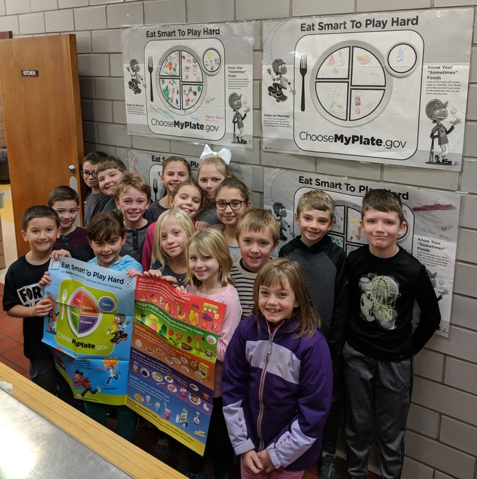 Children holding the cafeteria poster.