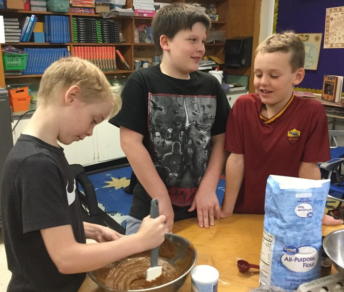 Three students stirring cake batter.